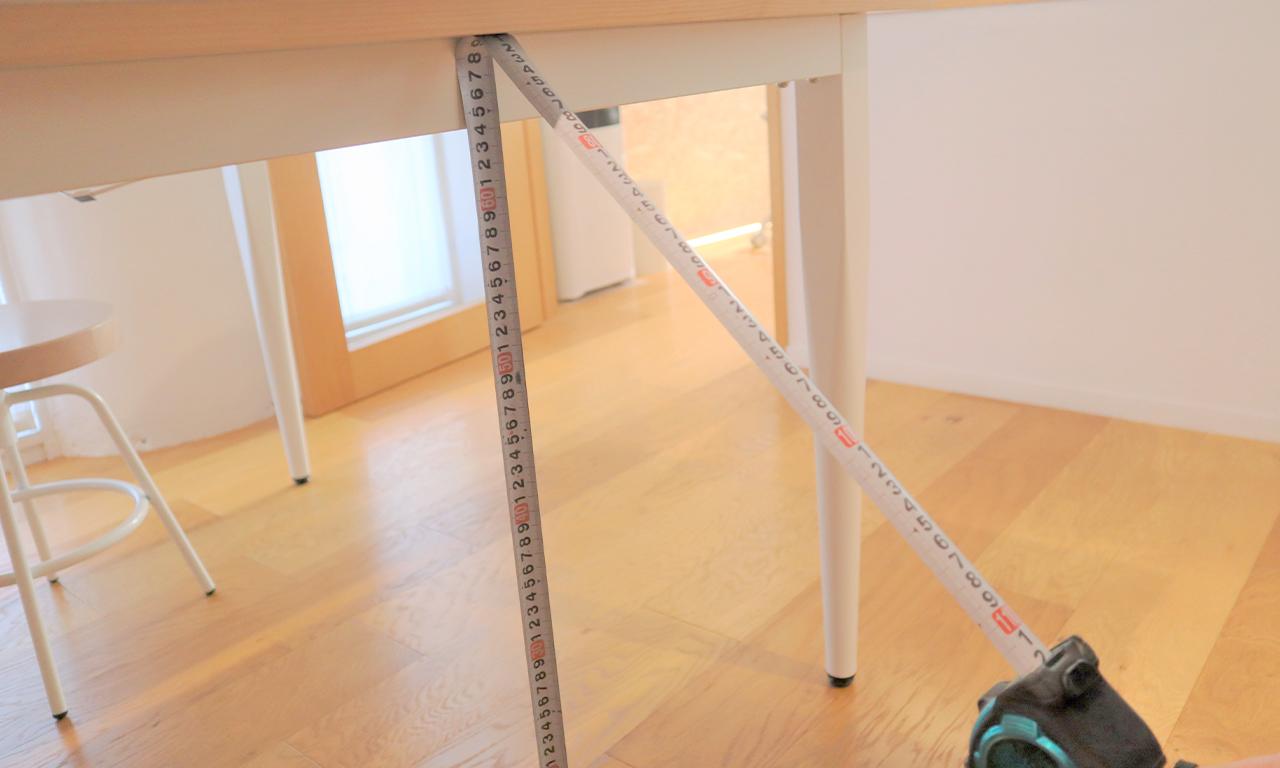 【スケールのテープ先端の爪を床に付け、爪を支点にテーブルの天板底面で鋼製テープをふわりと折り曲げて目盛を読みます。】